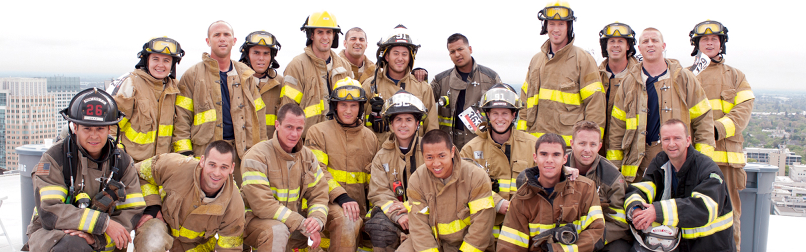 group of firefighters posing on a rooftop