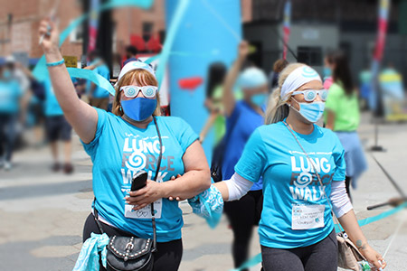 two women waving ribbons at a LUNG FORCE Walk